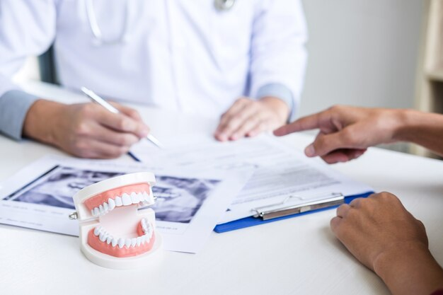Dentist writing report working with tooth x-ray film model and equipment used in the treatment