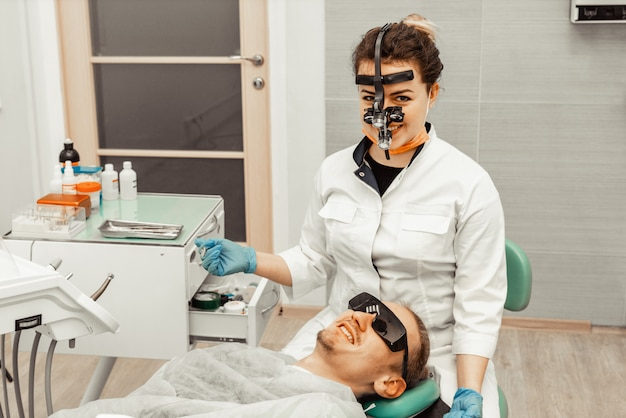 Dentist young woman treats a patient a man. the doctor uses disposable gloves, a mask and a hat. the dentist works in the patient's mouth, uses a professional tool.