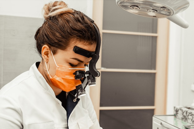 Dentist young woman treats a patient a man. the doctor uses disposable gloves, a mask and a hat