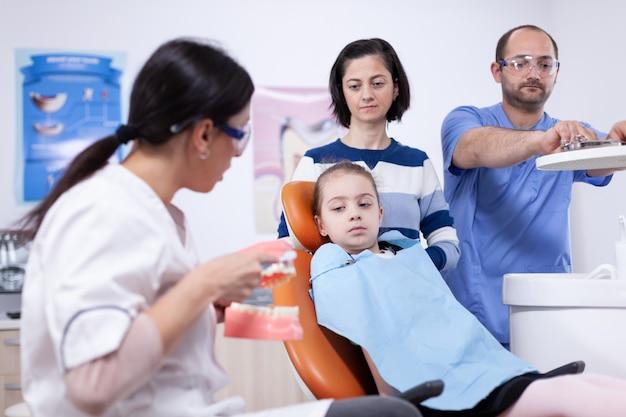 Врач-стоматолог объясняет оральное лечение с помощью модели челюсти. маленькая девочка и мать, слушая стоматолога, говорят о гигиене зубов в стоматологической клинике, держа модель челюсти.
