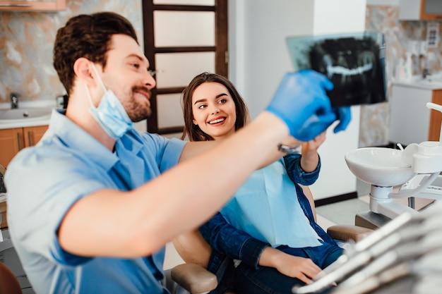 歯科およびヘルスケアの概念、歯科医院で女性患者に歯のx線を示す男性歯科医。