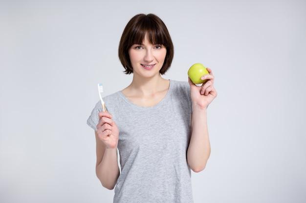 치과 및 교정 개념 - 회색 배경 위에 녹색 사과와 칫솔을 들고 치아에 교정기가 있는 젊은 여성의 초상화
