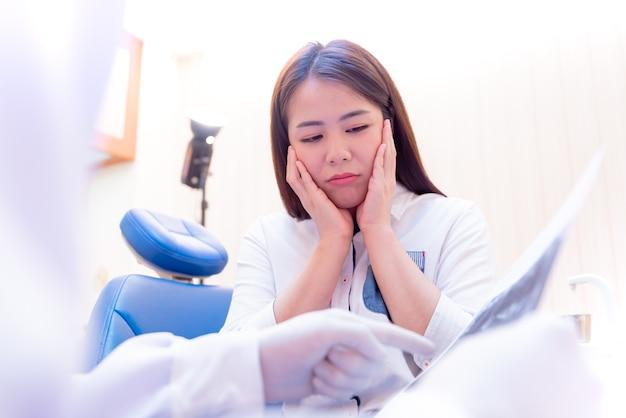 Стоматология и лечение зубов. зубы стоматолога осмотр для молодого азиатского пациента. образ жизни врача и работа в стоматологической клинике.