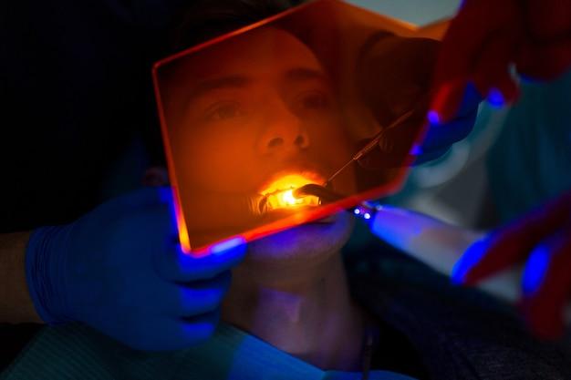 Стоматология. стоматолог и пациент. светоотверждаемая пломба. ультрафиолетовая стоматологическая лампа и оранжевое защитное стекло.