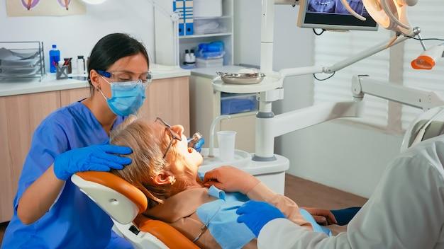 歯冠を取り除くために患者を準備する歯科医と看護師。口を開けて椅子に横たわっている口腔病学のオフィスで年配の女性の歯を治療する保護マスクを身に着けている歯科矯正医の技術者