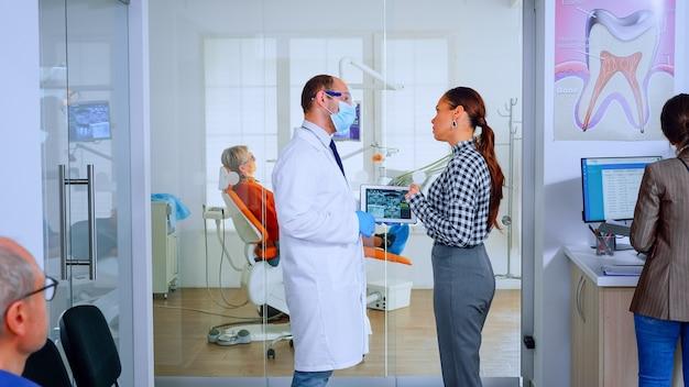 歯科医院の待機エリアに立っているタブレットを使用して患者に歯のx線写真を示す歯科医。混雑したオフィスでの治療を説明する女性と一緒に歯科x線撮影をレビューする口腔病学者