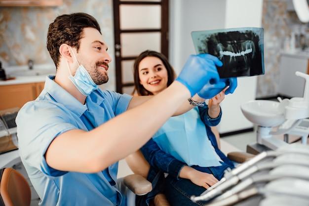 Odontoiatria e concetto di assistenza sanitaria, dentista maschio che mostra i raggi x dei denti al paziente femminile nella stanza della clinica odontoiatrica bianca.