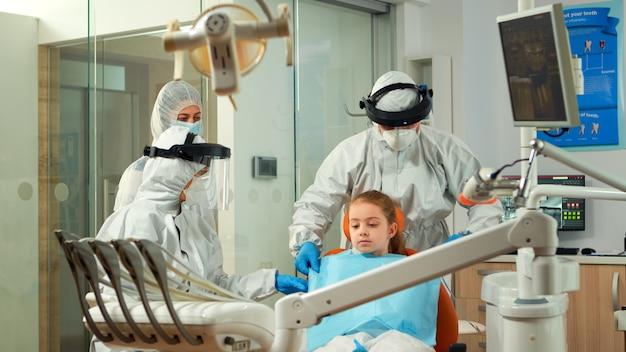 Covid-19パンデミック時の口腔病学的検査の前に子供に歯科用よだれかけを置くつなぎ服の歯科看護師。防護服を着たコロナウイルスの発生における新しい通常の歯科医の訪問の概念