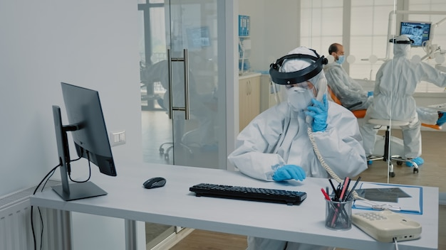 Dentistry nurse in protection suit sitting at desk