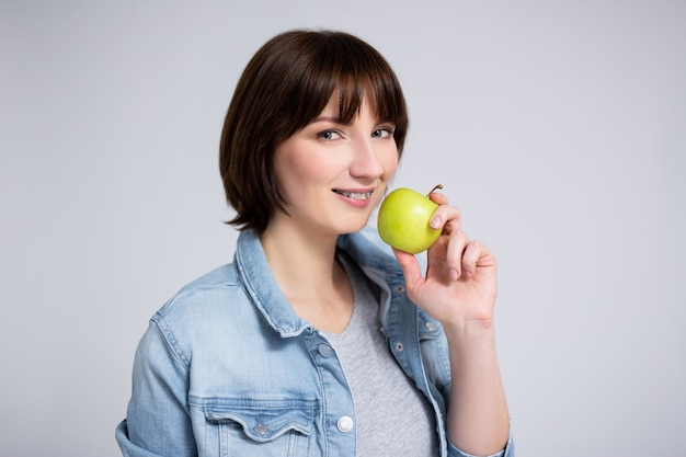 Dentistry and orthodontics concept - close up portrait of young woman or teenage girl with braces on teeth holding green apple over gray background