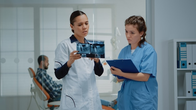 患者の歯のケアについて話し合う歯科矯正医の歯科チーム