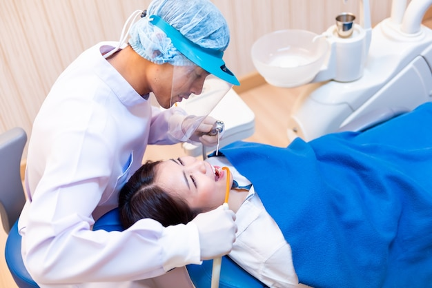 Dentistry and teeth healthcare concept at dental clinic. dentist check-up teeth for young asian patient.