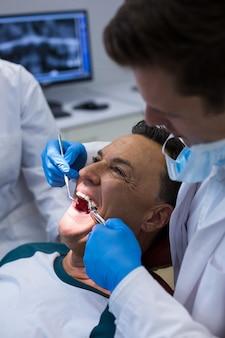 歯科医が男性患者をツールで調べる