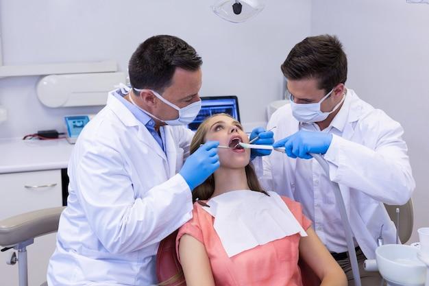 도구와 남성 환자를 검사하는 치과 의사