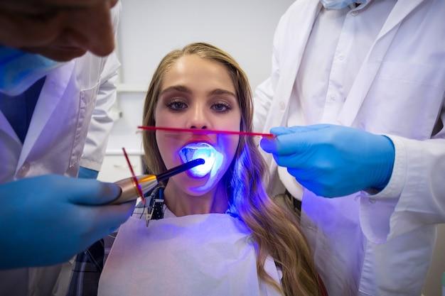 歯科医が歯科用硬化ライトで女性患者を調べる