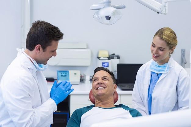 남성 환자와 상호 작용하는 치과 의사