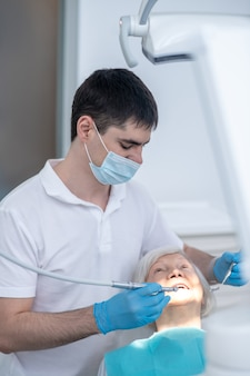 At the dentists. male dentist working with a senior patient with periodental disease