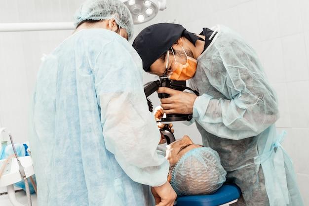 Стоматологи проведут операцию по установке имплантата. реальная операция. удаление зубов, имплантаты. здравоохранение оснащение врача рабочим местом. лечение зубов