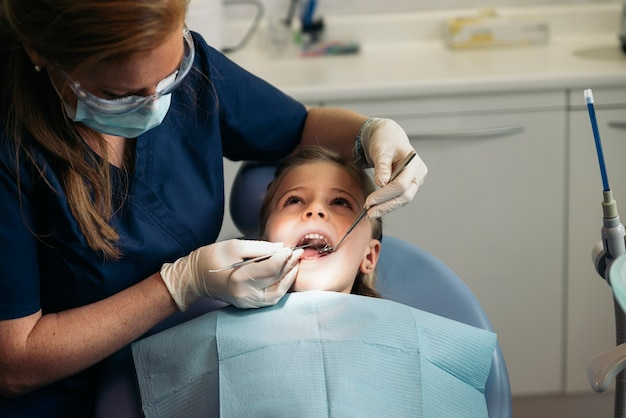 Стоматологи с пациентом во время стоматологического вмешательства девушке. концепция стоматолога