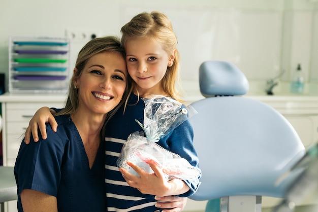 女の子への歯科介入中に患者と一緒にいる歯科医。歯科医の概念