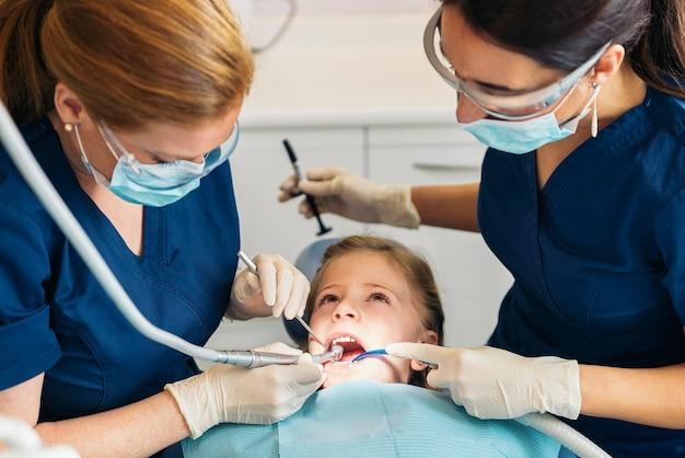女の子への歯科介入中に患者と一緒にいる歯科医。