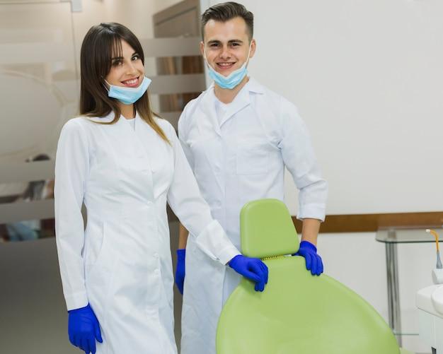 Стоматологи с хирургическими масками и перчатками позируют, улыбаясь