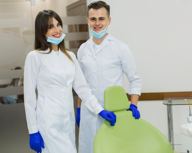 Dentists with surgical masks and gloves posing while smiling