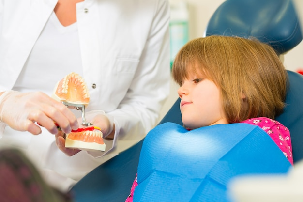 Dentistsurgery holds denture and explains a child patient with a toothbrush