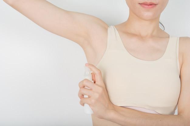 Deodorant spray on white armpit and underarm skin treatment
