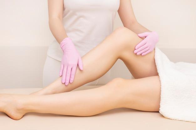 脱毛とマッサージ。滑らかな肌を持つ美しい女性の足。脱毛マスター、手袋をしたマッサージ師。