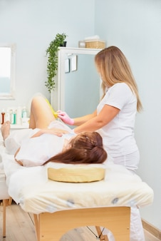 Depilation and beauty concept -beautician depilating young womans legs with liquid sugar in spa center. depilation of legs with yellow shugaring paste