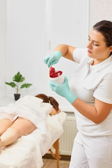 Depilation and beauty concept - beautician waxing young woman