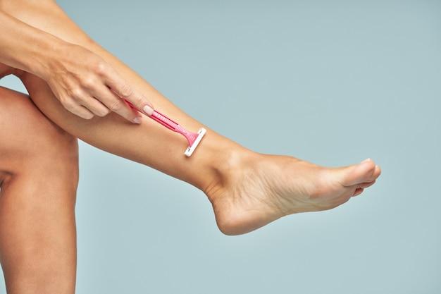 Depilation close up of lady shaving her leg with safety razor isolated on blue background