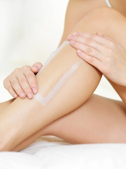 Depilation of female legs by wax
