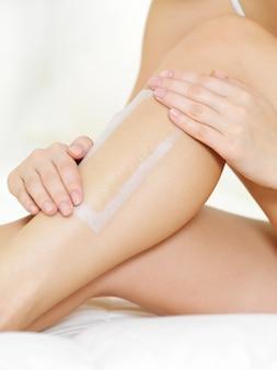 Depilazione delle gambe femminili con la cera