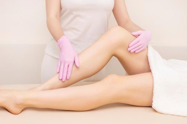 Depilation and massage. beautiful female legs with smooth skin. depilation master, masseur with gloves.