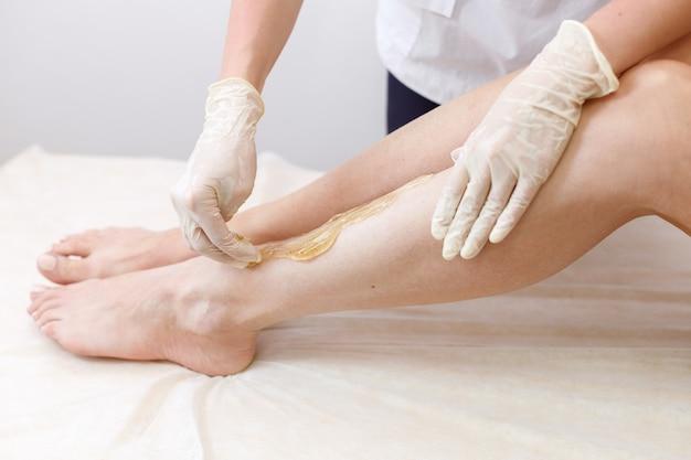 Depilation master applies sugaring paste legs