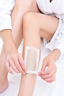 Depilation on the part of female legs with waxing - white space