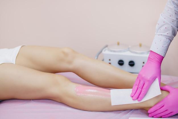 Процедура депиляции воском на ногах