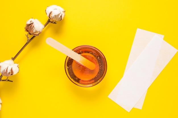 노란색 배경에 나무 주걱으로 제모 설탕 페이스트 제모 제모