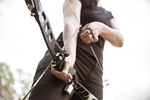アーチェリーの弓から撃つために矢を配備する