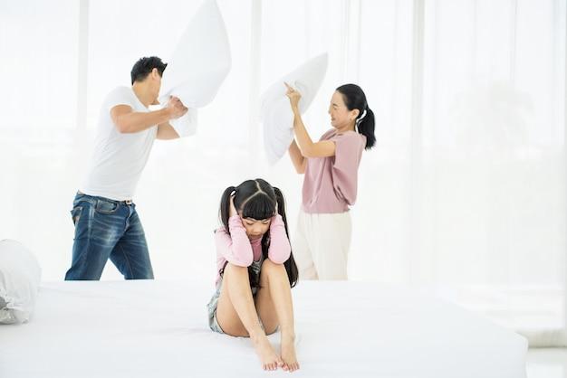 憂鬱なアジアの女の子の子供は、バックグラウンドで一緒に枕投げを使用して議論をしている両親と彼女の耳を覆います