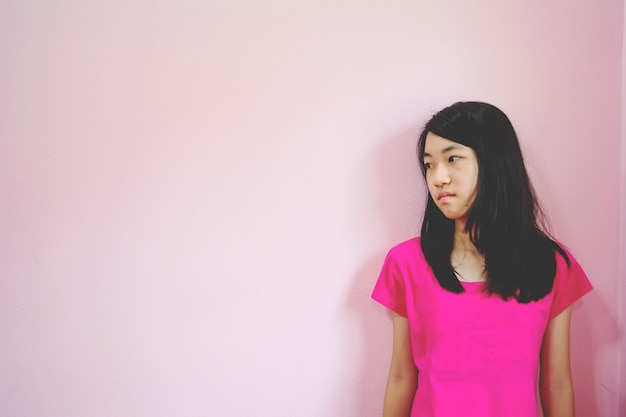 Depress and hopeless girl with absent minded looking down stand on pink background