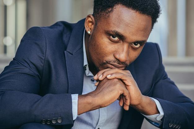 カメラを見て落ち込んでいるアフリカ系アメリカ人の実業家のクローズアップの肖像画