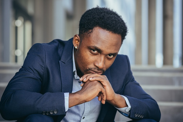 Depressed african american businessman looking at camera close up portrait