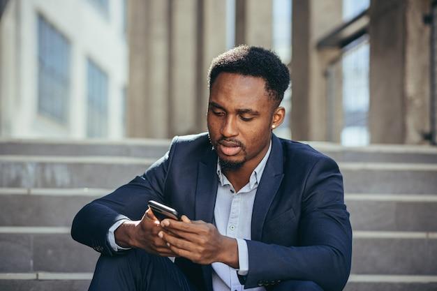 우울한 아프리카계 미국인 사업가가 휴대폰에서 나쁜 소식을 읽고, 비즈니스 정장을 입고 계단에 앉아 좌절하고 슬퍼합니다. 프리미엄 사진