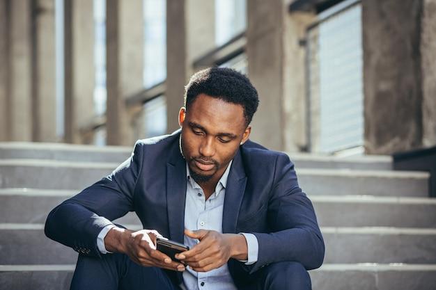 우울한 아프리카계 미국인 사업가가 휴대폰에서 나쁜 소식을 읽고, 비즈니스 정장을 입고 계단에 앉아 좌절하고 슬퍼합니다.