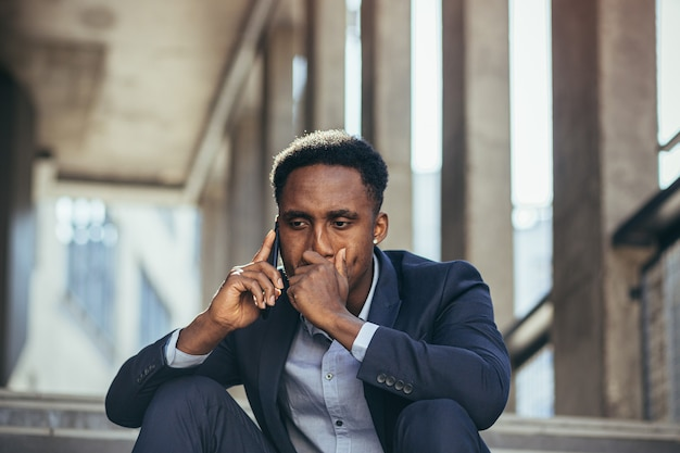 Depressed african american businessman telling sad news talking on cell phone sitting on office stairs in business suit