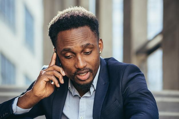 ビジネススーツでオフィスの階段に座って携帯電話で話している悲しいニュースを語る落ち込んでいるアフリカ系アメリカ人のビジネスマン