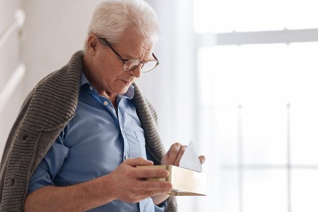 Подавленный пожилой симпатичный мужчина держит коробку и кладет в нее свои старые письма, стоя у окна
